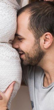 hombre apoyado en embarazada